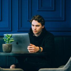 Man kijkt op zijn laptop