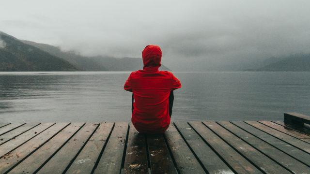 Eenzaam persoon zittend op een pier