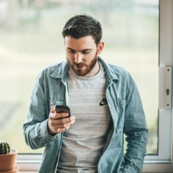 Man kijkt op zijn telefoon